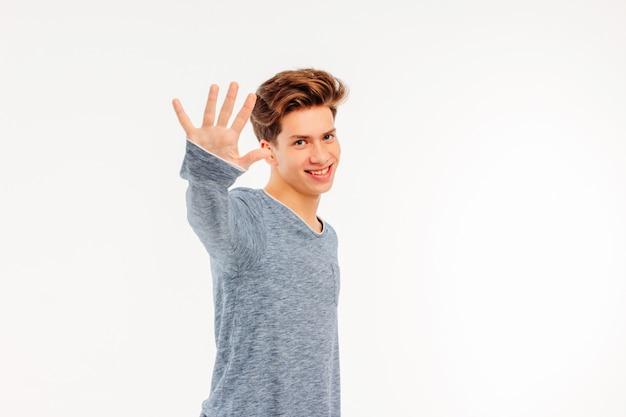 Il giovane tipo sorridente dà il benvenuto a dire arrivederci alla mano su backg bianco