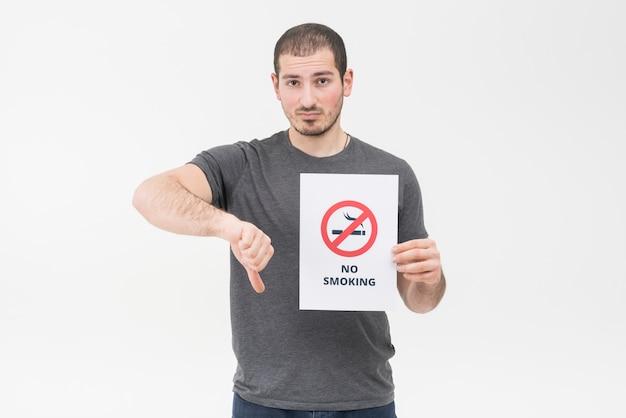 Il giovane triste che tiene il segno non fumatori che mostra il pollice giù gesture contro fondo bianco