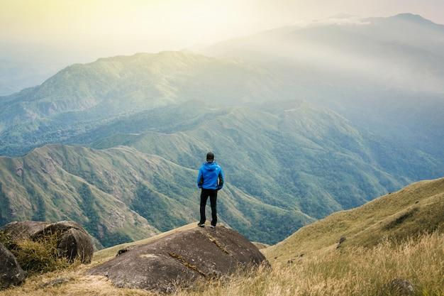 Il giovane turista dell'asia alla montagna sta guardando sopra l'alba nebbiosa e nebbiosa del mattino