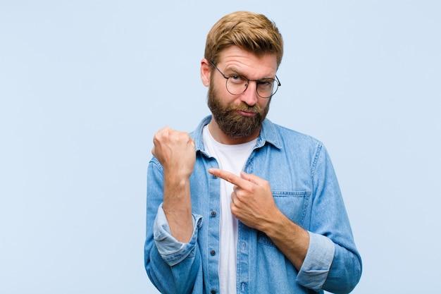 Il giovane uomo adulto biondo che sembra impaziente e arrabbiato, indicando l'orologio, chiedendo puntualità, vuole essere puntuale
