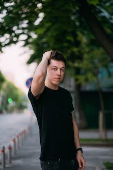 Il giovane uomo adulto in maglietta nera e jeans cammina su una via della città
