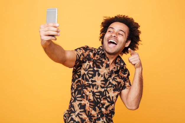Il giovane uomo africano felice fa il selfie mentre indica