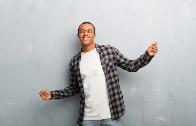 Il giovane uomo afroamericano con la camicia a quadretti gode di di ballare