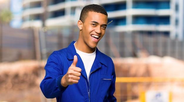 Il giovane uomo afroamericano del lavoratore che dà un pollice aumenta il gesto perché qualcosa di buono è successo in un cantiere