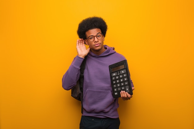 Il giovane uomo afroamericano dello studente che tiene un calcolatore prova ad ascoltare un gossip