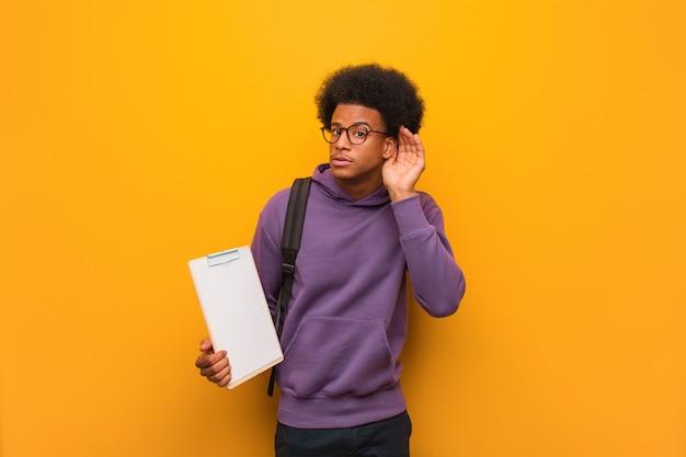 Il giovane uomo afroamericano dello studente che tiene una lavagna per appunti prova ad ascoltare un gossip