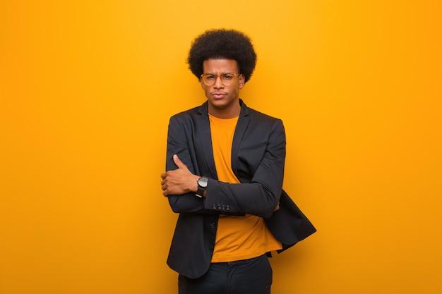 Il giovane uomo afroamericano di affari sopra un incrocio arancio della parete arma rilassato