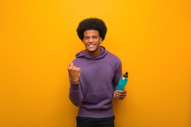 Il giovane uomo afroamericano di forma fisica che tiene una bevanda di energia ha sorpreso e colpito