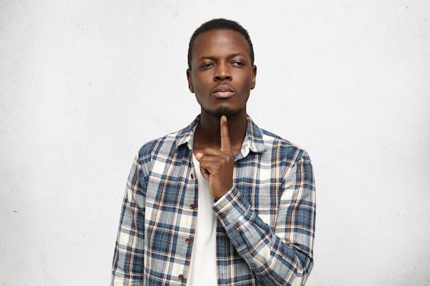 Il giovane uomo afroamericano pensieroso premuroso che indossa la camicia a quadretti alla moda sopra la maglietta bianca tiene il dito indice al suo mento mentre prova a ricordare qualcosa