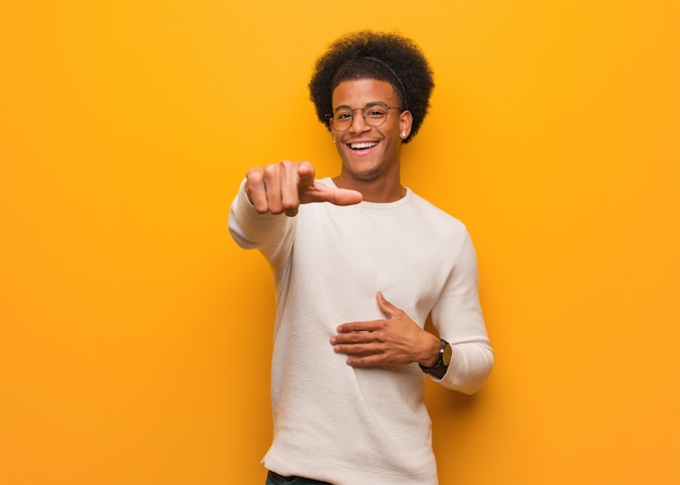 Il giovane uomo afroamericano sopra una parete arancio sogna di raggiungere gli scopi e gli scopi