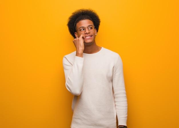 Il giovane uomo afroamericano sopra una parete arancione ha rilassato il pensiero a qualcosa che esamina uno spazio della copia