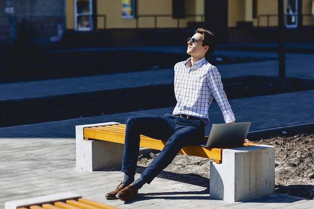 Il giovane uomo alla moda lavora al computer portatile al parco il giorno soleggiato
