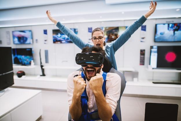 Il giovane uomo allegro celebra la vittoria in una partita mentre usa la realtà virtuale e la sua ragazza festeggia con lui.