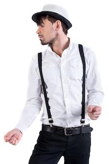 Il giovane uomo alto in camicia bianca e cappello bianco sta ballando.
