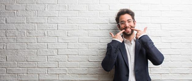 Il giovane uomo amichevole di affari sorride, indicando la bocca, concetto dei denti perfetti, denti bianchi