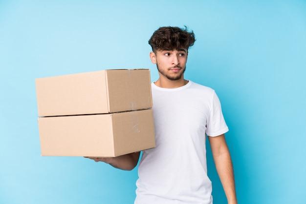 Il giovane uomo arabo che tiene le scatole isolate confuso, si sente dubbioso e incerto.