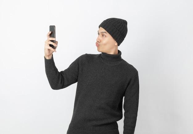 Il giovane uomo asiatico bello che porta il maglione e il beanie grigi mentre gioca lo smartphone e prende un selfie