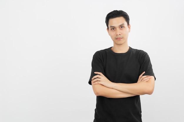 Il giovane uomo asiatico bello che sorride e che esamina la macchina fotografica con le armi ha attraversato isolato