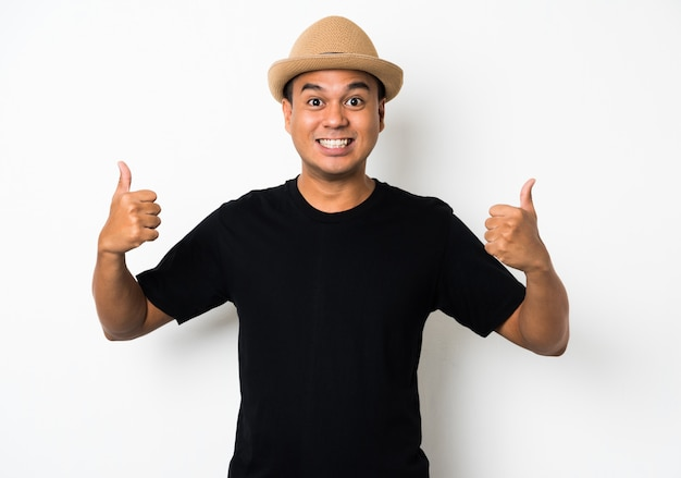 Il giovane uomo asiatico con il cappello sente lo shock e la sorpresa con un'espressione eccessiva del viso.