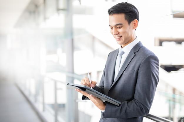 Il giovane uomo asiatico di affari sorride facendo uso di una compressa