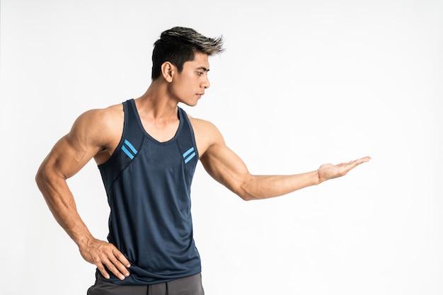 Il giovane uomo asiatico muscolare in abiti sportivi sta lateralmente con qualcosa presente sulla sua mano