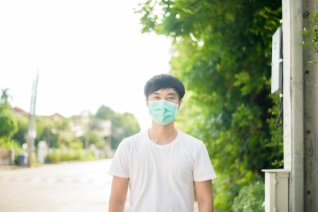 Il giovane uomo asiatico sta indossando la maschera in città all'aperto