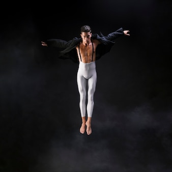 Il giovane uomo atletico che salta con le mani estese si avvicina al fumo contro il fondo nero