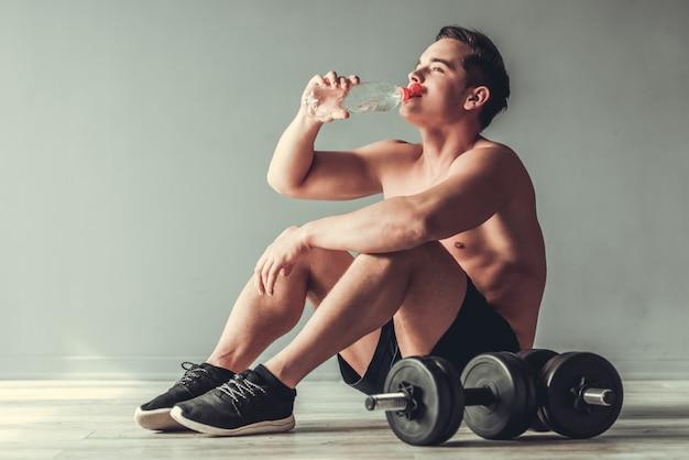 Il giovane uomo attraente beve l'acqua e riposa sul pavimento.