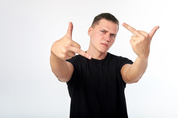 Il giovane uomo attraente che porta la rappresentazione nera della camicia scopa firmare sulla parete bianca