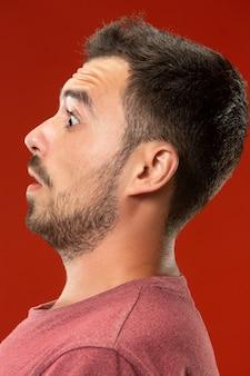 Il giovane uomo attraente che sembra sorpreso isolato su rosso