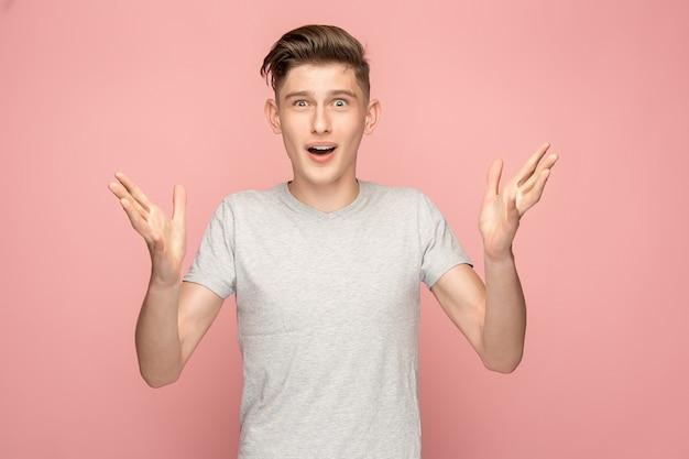 Il giovane uomo attraente che sembra sorpreso isolato sul rosa
