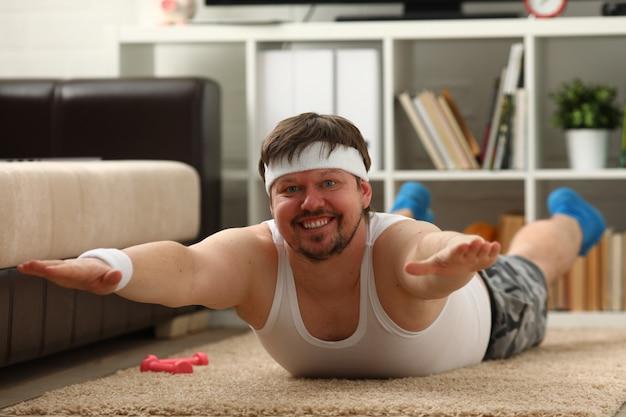 Il giovane uomo attraente di forma fisica si trova su una stuoia grassa con