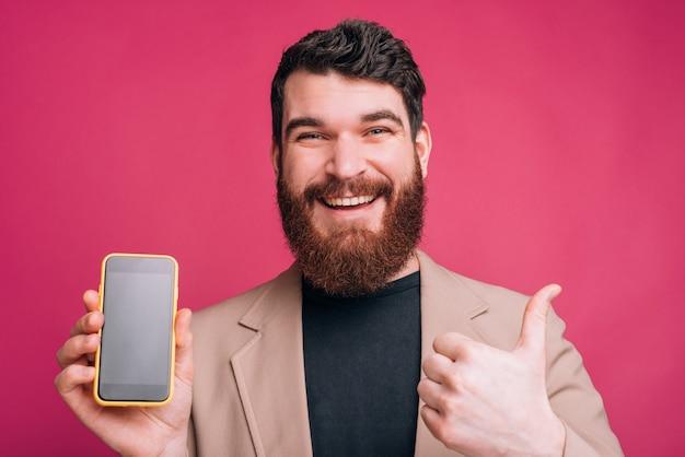 Il giovane uomo barbuto allegro sta mostrando il suoi telefono e pollice dello schermo in bianco su sulla parete rosa