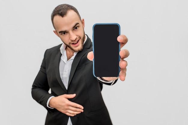 Il giovane uomo barbuto sicuro in vestito tiene il telefono vicino alla macchina fotografica. sembra dritto. guy tiene un'altra mano sullo stomaco.
