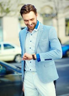 Il giovane uomo bello alla moda in vestito nella via guarda il suo orologio