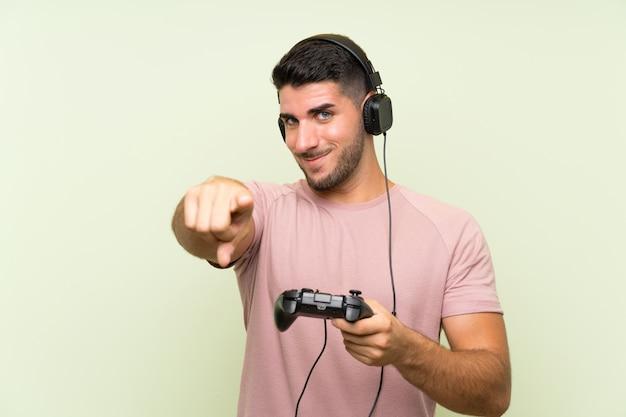 Il giovane uomo bello che gioca con un regolatore del videogioco sopra la parete verde indica il dito con un'espressione sicura