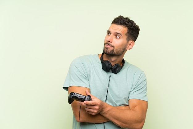 Il giovane uomo bello che gioca con un regolatore del videogioco sopra la parete verde isolata che fa i dubbi gesturing mentre solleva le spalle