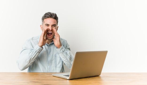 Il giovane uomo bello che lavora con il suo gridare del computer portatile ha eccitato alla parte anteriore.