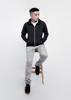 Il giovane uomo bello che porta la chiusura lampo nera della felpa con cappuccio è seduto su una sedia mentre posa isolato su priorità bassa