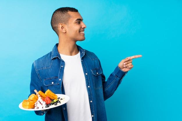 Il giovane uomo bello che tiene le cialde sopra la parete blu isolata che indica il lato per presentare un prodotto