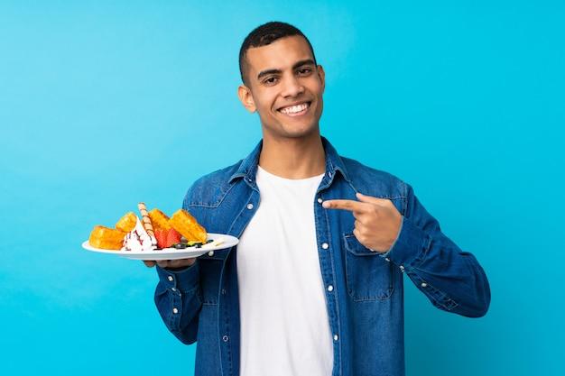 Il giovane uomo bello che tiene le cialde sopra la parete blu isolata e lo indica