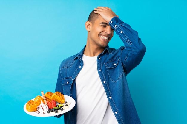 Il giovane uomo bello che tiene le cialde sopra la parete blu isolata ha realizzato qualcosa e intendendo la soluzione