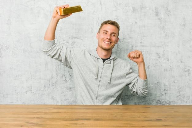 Il giovane uomo bello che tiene un lingotto d'oro su una tavola che celebra un giorno speciale, salta e alza le braccia con energia.