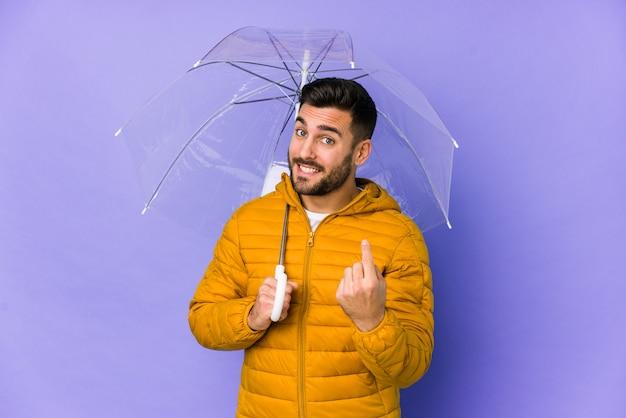 Il giovane uomo bello che tiene un ombrello ha isolato indicare con il dito come se l'invito si avvicini.