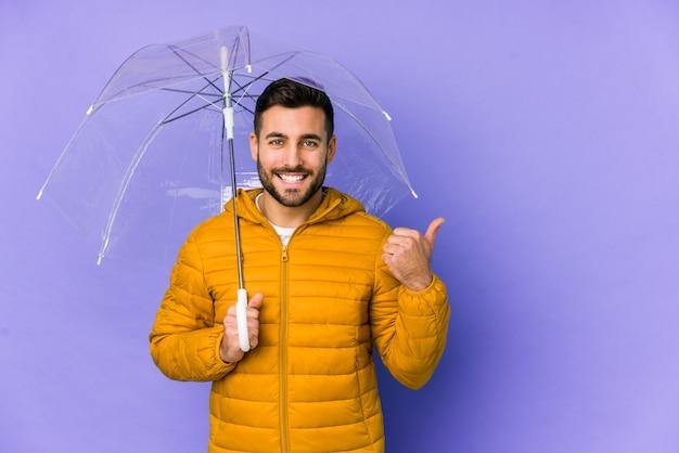 Il giovane uomo bello che tiene un ombrello ha isolato sorridere e sollevare il pollice in su