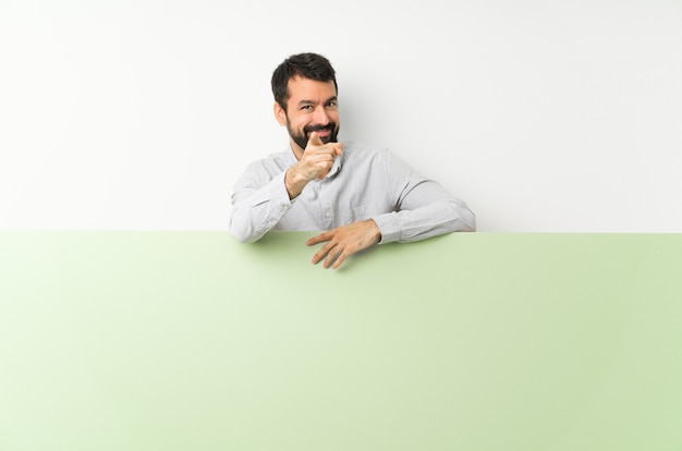 Il giovane uomo bello con la barba che tiene un grande cartello vuoto verde indica il dito con un'espressione sicura