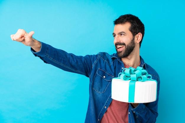 Il giovane uomo bello con una grande torta sopra la parete blu isolata che dà pollici aumenta il gesto