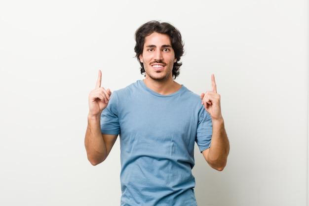 Il giovane uomo bello contro una parete bianca indica con entrambe le dita anteriori in su che mostrano uno spazio.