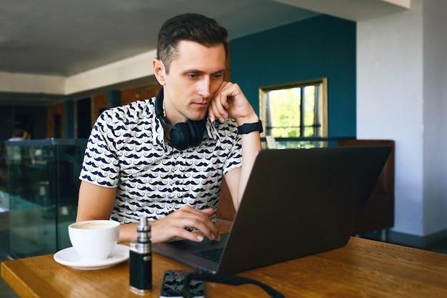 Il giovane uomo bello dei pantaloni a vita bassa in occhiali da sole sta utilizzando il computer portatile nella caffetteria.