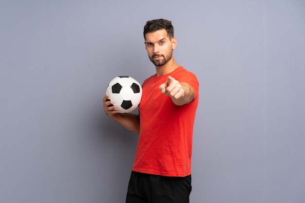 Il giovane uomo bello del giocatore di football americano sopra la parete bianca isolata indica il dito voi con un'espressione sicura